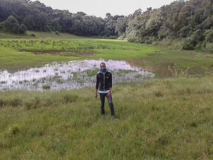 Alfred Mepukori standing near Ilturot natural water catchment area in Naimina Enkiyio Forest